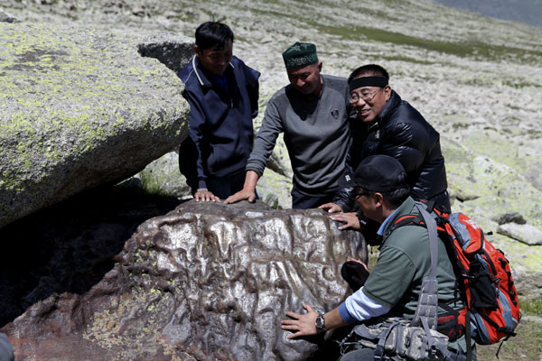 Astronomers inspect a big stony-iron meteorite that was found in Altay prefecture, Xinjiang Uygur autonomous region, on July 17, 2011. The above-earth part of the rock is 2.2 meters long and 1.25 meters tall, with a width of 1.2 meters (average data). Its weight is estimated at 25 tons. [Photo/Xinhua]