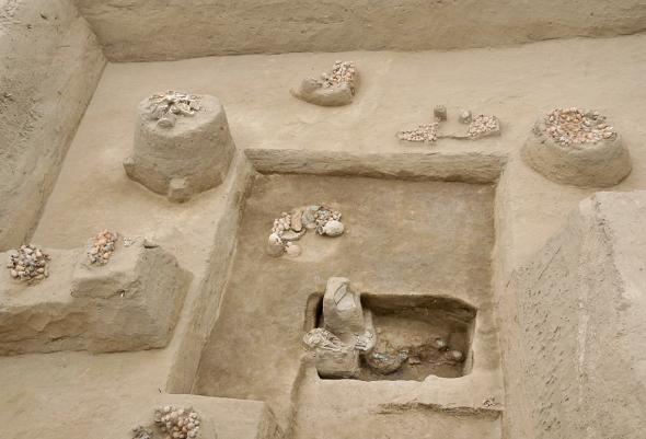 Ceramic vessels and other offerings surround the grave of the elite 14th-century executioner. PHOTOGRAPH COURTESY CARLOS WESTER LA TORRE