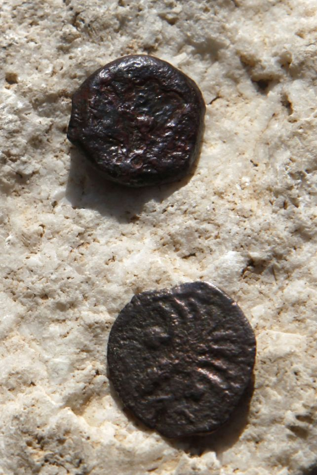 JERUSALEM, ISRAEL - NOVEMBER 23: (ISRAEL OUT) Two ancient bronze coins, which according to Israel Antiquities Authority archaeologists were struck by the Roman procurator of Judea, Valerius Gratus, in the year 17/18 CE and recently were revealed in excavations beneath the Western Wall in Jerusalem's Old City are exposed to the media on November 23, 2011 in Israel. Archaeologists in Jerusalem have uncovered coins inside an ancient Jewish ritual bath by the Wailing Wall in the Old City which challenge the assumption that all of the walls of the Second Jewish Temple were built by King Herod. (Photo by Lior Mizrahi/Getty Images) Israeli Archaeologists Rethink Herod's Role In Western Wall Construction