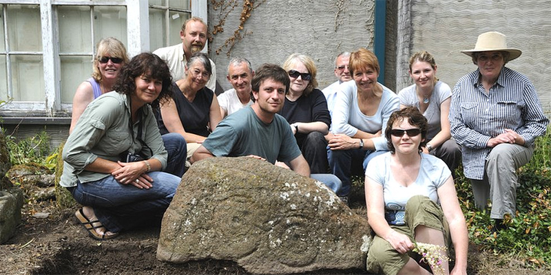 Meet the Welsh Rock Art Organisation team. Experts Dr George Nash, Adam Stanford, Tom Wellicome, Carol James and Cat Rees are helped by a large and changing pool of students, other professional archaeologists and enthusiasts. Here are some of them at the current home of the Llwydiarth Esgob Stone.