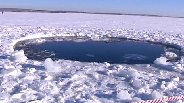 Footage shows an icy lake near Chebarkul, where police say a meteorite landed