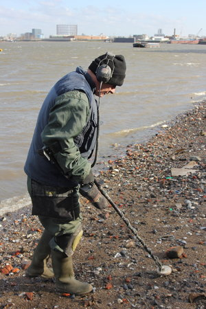 Mike Woodham uses a metal detector to search for historic artifacts on the banks of the Thames in London. Mudlarks like Woodham contribute important objects to museums, but some think their methods are too destructive. - Christopher Werth for NPR