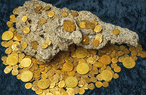 Hundreds of coins rest with a piece of bedrock shortly after they were pulled from the Atlantic Ocean off the coast of Vero Beach, FL.