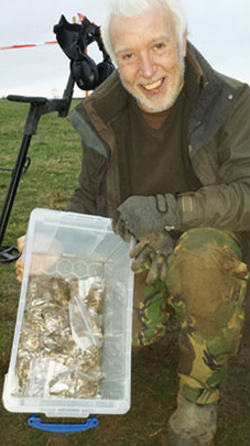 Finder Paul Coleman holds some of the humongous hoard that he discovered