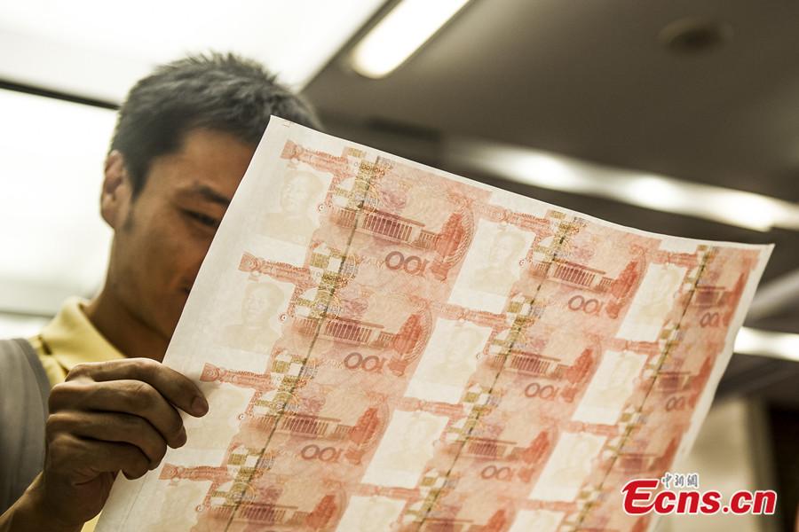 A Guangdong police officer examines a sheet of film used to print fake Chinese bank notes. [Photo: China News Service / Long Yuyang]