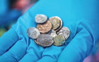 Twenty-six Late Iron Age and Roman coins were unearthed inside a cave in Derbyshire, England